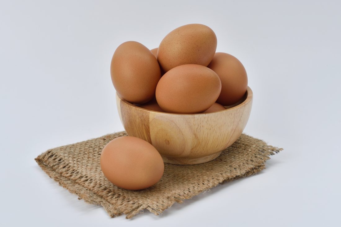 Image is of a number of chicken eggs piled up in a brown wooden bowl, with one egg lying beside the bowl on a small patch of jute cloth. The background is a pale blue with no other detail.