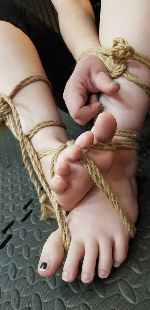Image is of a pair of feet belonging to a white person (Morgan) bound together with hemp rope, some of which runs between the toes and binds one wrist to one ankle as well. Morgan is wearing teal nail polish on their fingers and none on their toes, and the background is a black patterned floor mat.