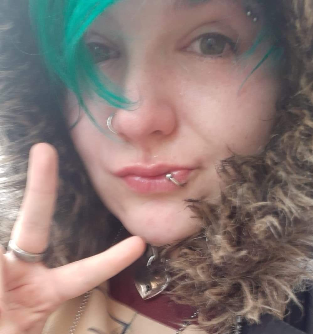 Image is a selfie of Morgan, a white blue-haired nonbinary person with multiple facial piercings, who appears to have been crying very recently: their nose is pink, their face is damp and their mouth is sort of pulled off to one side because they are too sad to smile. They're holding two fingers up to the camera in the peace sign and their face is framed by the fluffy hood of their coat.